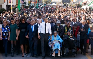Barack Obama, center, walks as he holds hands with Amelia Boynton Robinson and John Lewis as they walk across the Edmund Pettus Bridge in Selma, Alabama, for the 50th anniversary of Bloody Sunday, in 2015.