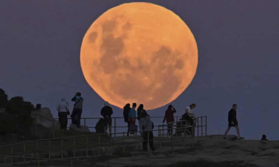 People watch as the 'super flower blood moon' rises over Bondi Beach in Sydney on 26 May, 2021. Guardian Australia's picture editor explains how to photograph the moon whether you're using a phone or DSLR camera, and the best settings to use.