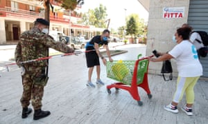 A woman delivers a cart with food for people in quarantine at a residential complex in Mondragone.