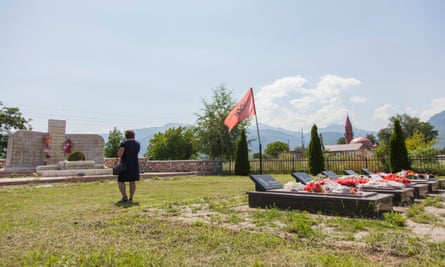 A large memorial bearing 46 names stands before a row of five tombs in the mountain village of Beleg, Kosovo