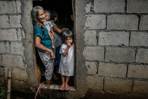 Remy Fernandez, 84, holds her grandchild, RJ, in the front door of her cinder block house in Payatas, Metro Manila