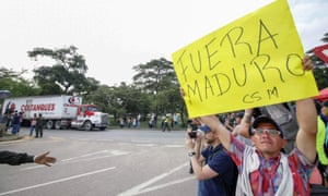 A demonstrator in Cúcuta welcomes aid trucks with a placard saying 'Maduro out'.