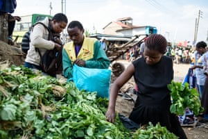 Rebecca Awuor buys greens from a market stall and loads them into her reusable bag.