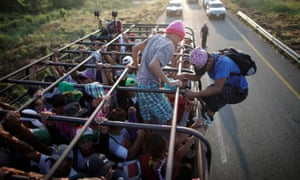 Migrants hitchhike on a truck along the highway to Arriaga from Pijijiapan, Mexico, on 26 October.