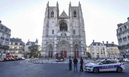 French police officers inspect the partially burnt facade of the Cathedral of St Peter and St Paul in Nantes, western France