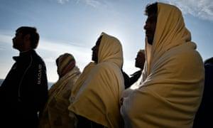 Migrants in blankets on boat