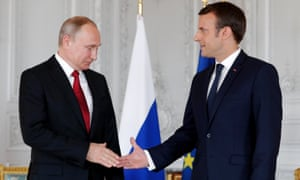 Emmanuel Macron shakes hands with Vladimir Putin as they meet for talks before the opening of an exhibition marking 300 years of diplomatic ties between France and Russia.