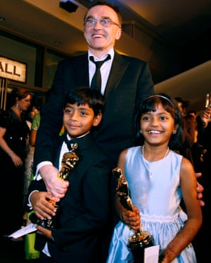 Danny Boyle poses with young actors and two of Slumdog Millionaire's eight Oscars.