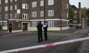 Police officers stand guard near the scene of the fatal stabbing in Tulse Hill, south London.