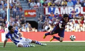 Real Sociedad's Mexican forward Carlos Vela, left, tackles Barcelona's defender Marc Bartra