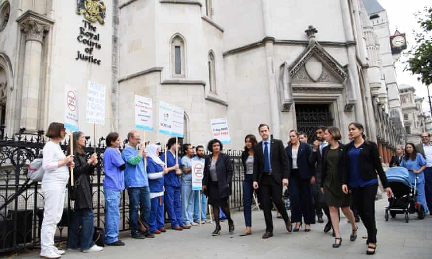 Doctors from Justice for Health walk past supporters outside the Royal Courts of Justice.