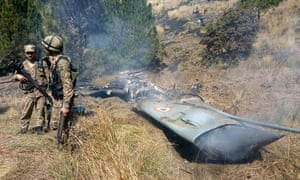 Pakistani soldiers stand next to what Pakistan says is the wreckage of a shot down Indian fighter jet in Pakistan-controlled Kashmir.