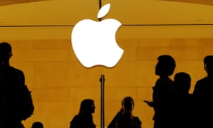 Customers walk past an Apple logo inside an Apple store at Grand Central Station in New York.