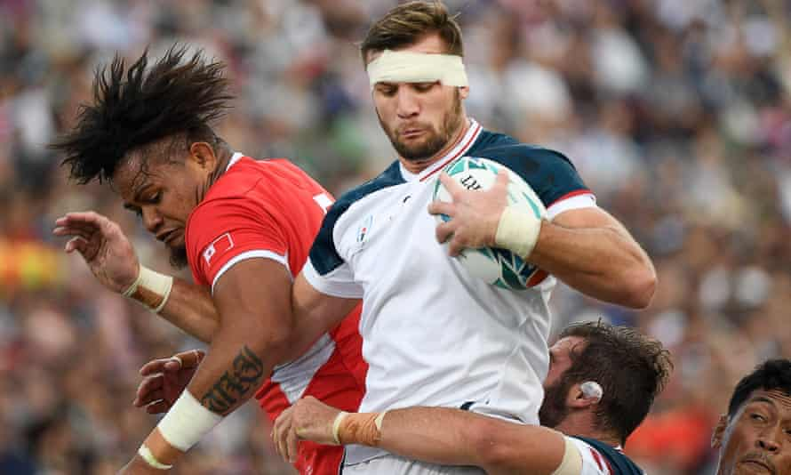 US No8 Cam Dolan catches the ball next to Tonga lock Leva Fifita during a World Cup game in Japan in 2019.