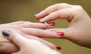 A woman places a wedding ring on her partner's finger.