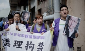Protesters hold pictures of Chinese human rights lawyer Pu Zhiqiang