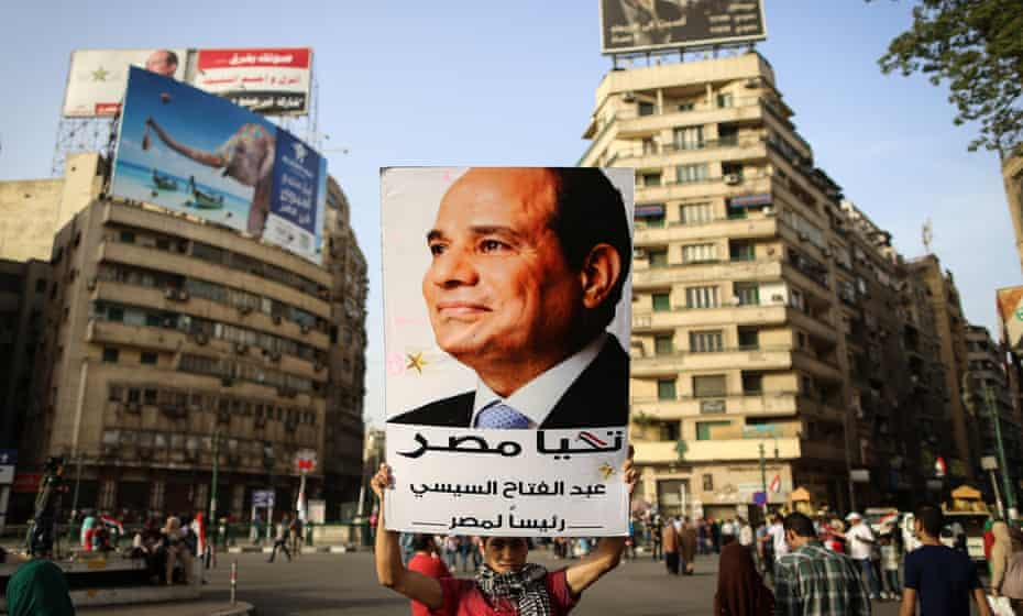 A man holds up a portrait of the Egyptian president, Abdel Fatah al-Sisi, in Cairo's Tahrir Square