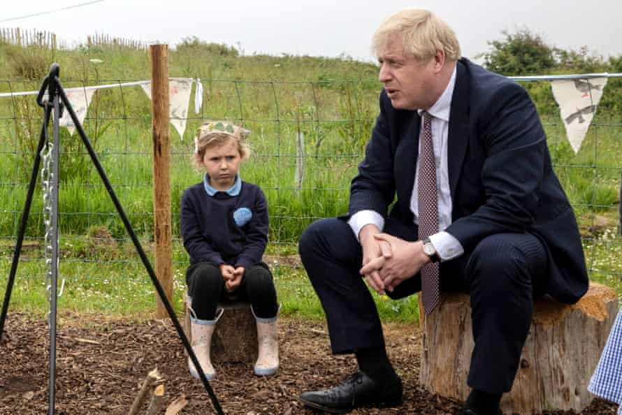 Boris Johnson visits a primary school with an angry looking small child