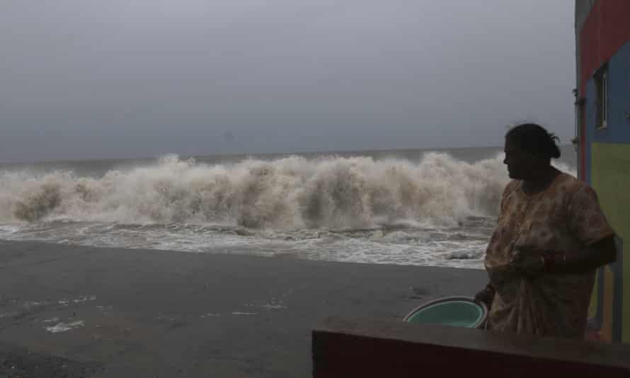 A woman watches waves splash on shores of the Arabian Sea in Mumbai.