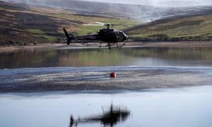 A helicopter scoops up water to tackle the blaze near Saddleworth Moor