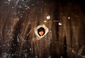 GazaA child checks a house that was ablaze taking the life of three children after a fire was ignited by a candle used to light up their room during a power cut in al-Nusirat refugee camp