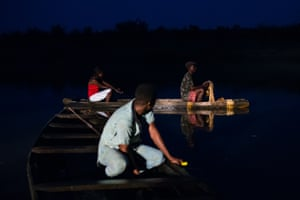 Three people in fishing canoes at night