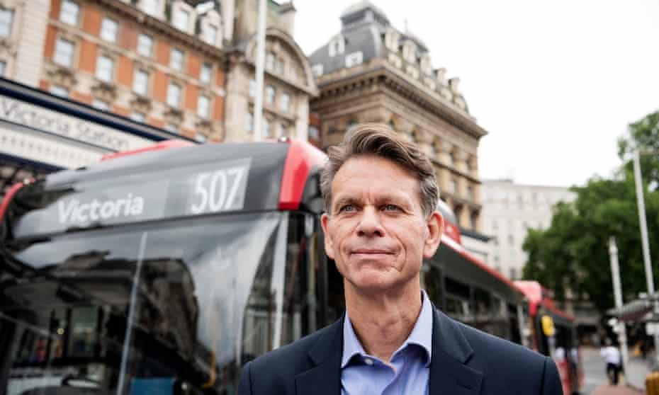 Head and shoulders shot of David Brown in a suit and open-necked shirt standing in front of a red number 507 single-decker bus, with the facade of Victoria station in the background