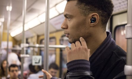 a man on the tube wearing bragi the dash earpieces