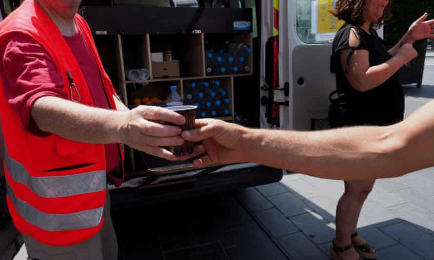 Red Cross workers hand out water to homeless people in Tours amid sweltering conditions.
