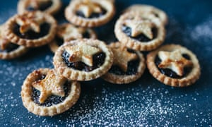 a stack of mince pies dusted with icing sugar