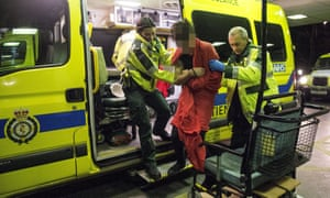Paramedics help a drunken man in to A&E in central London