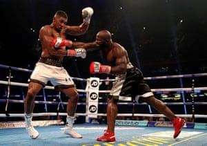 Anthony Joshua takes evasive action as Carlos Takam fights back.
