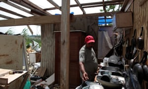 A man in Puerto Rico sorts through the remains of his home.