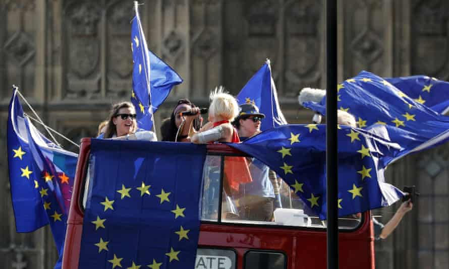 Anti-Brexit demonstrators wave EU flags on a bus driving by Parliament Square