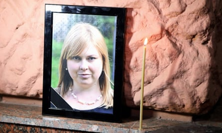 A candle burns by a portrait of Kateryna Handzyuk during a rally in Ukraine after her death.
