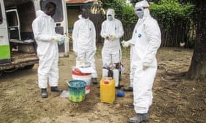 Health workers prepare to enter the house of a person suspected to have died of Ebola on the outskirts of Freetown, Sierra Leone.