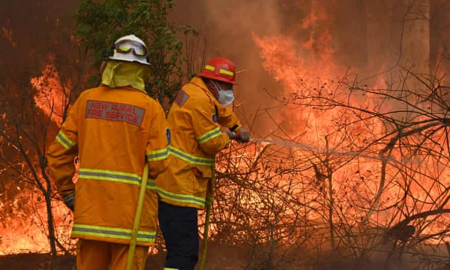 Firefighters tackle a bushfire to save a home in Taree, 350km north of Sydney