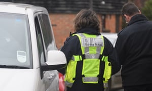A Border Force officer fills in paperwork after stopping a group of men in Lydd, Kent.