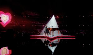 elton john spotlit on stage at a grand piano wearing a frock coat