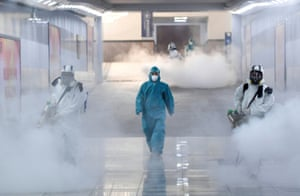 Volunteers in protective suits disinfect a railway station as China continues to be hit by the coronavirus outbreak.