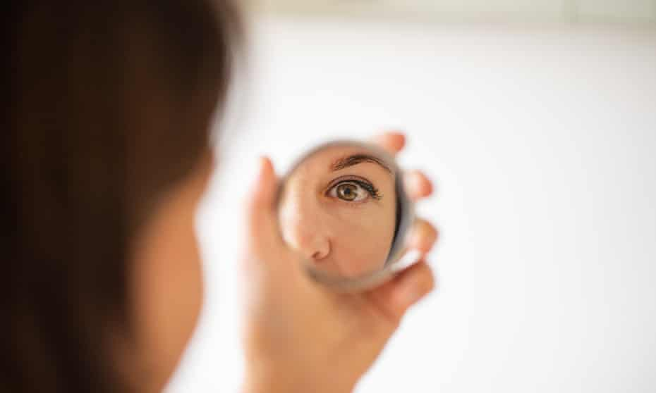 Woman looking at herself in the mirror.