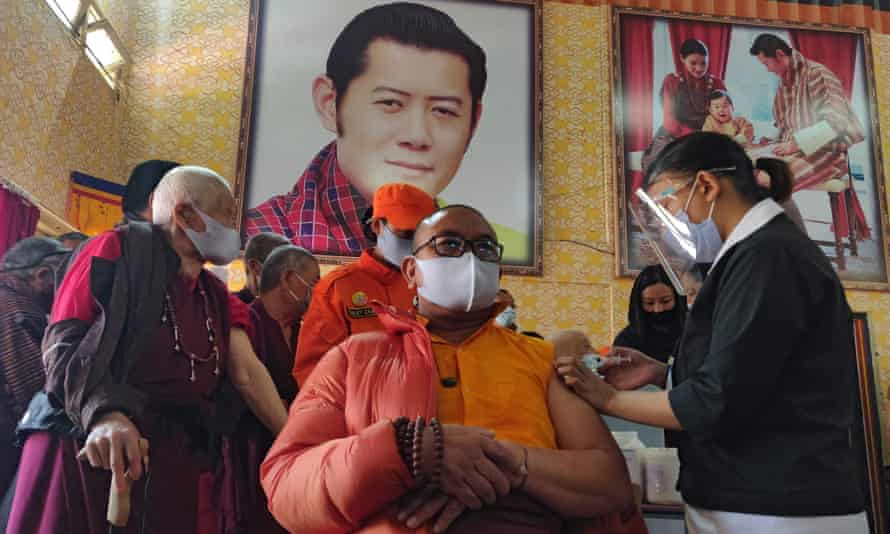 A health worker inoculates a dose of a COVID-19 coronavirus vaccine to a Buddhist monk sitting in front of a portrait of Bhutan's King Jigme Khesar Namgyel Wangchuck (top C) during the first day of vaccination in Bhutan, at Lungtenzampa Middle Secondary school in Thimphu.