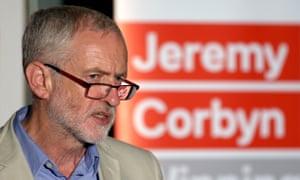 Jeremy Corbyn speaking in front of a Jeremy Corbyn poster
