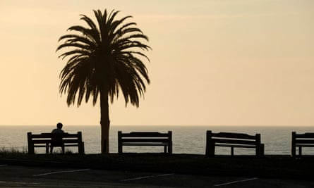 A young man sits alone next to empty park benches during the outbreak of the coronavirus in Encinitas, California, 30 March 2020.