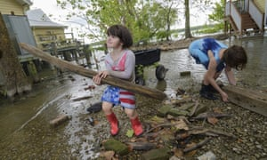 Delilah Campbell, four, left, and her sister, Tallulah Campbell, eight, clear out driftwood and other debris in preparation of Tropical Storm Barry near New Orleans on Thursday.