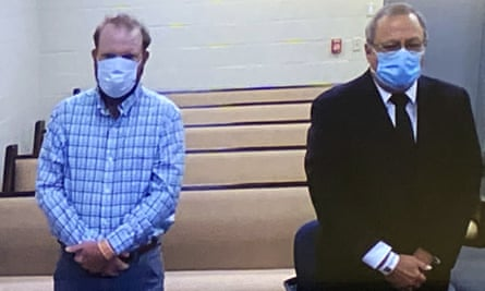 In this image made from video, Travis McMichael, left, and Greg McMichael listen to a preliminary hearing via a court video feed on Thursday in the Glynn County jail, in Brunswick, Georgia.