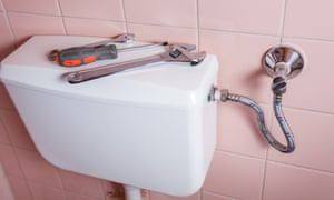 Plumbing tools (wrench, spanner, screwdriver) lying on toilet cistern, with pink tiles behind