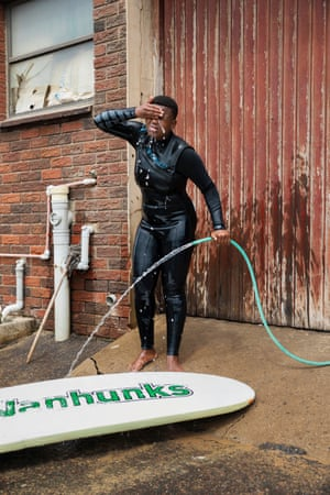 Ndzanibe washes her board down after surfing