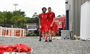 Mohamed Salah and James Milner share a joke during a training session