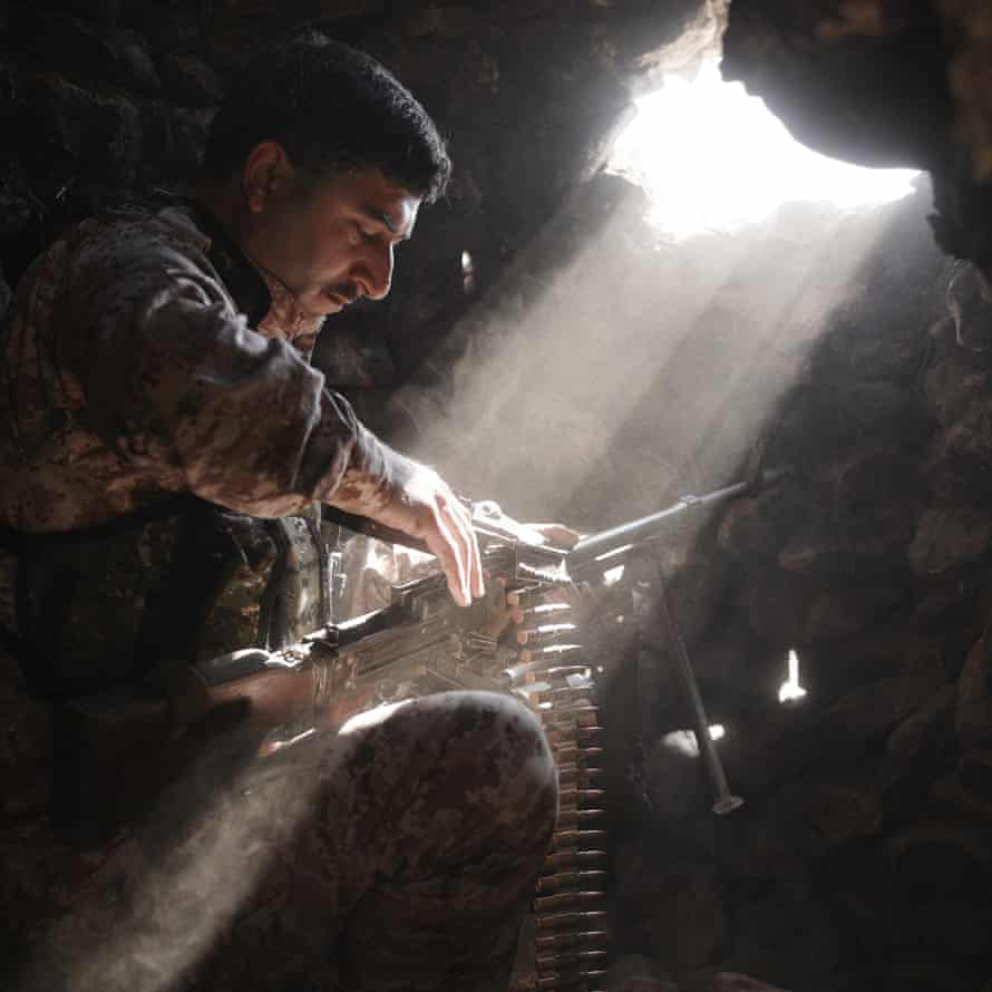 Ahmed Zakwan, a rebel fighter of the Army of Revolutionaries, reloads his PK machine gun in a farmhouse facing a small hamlet under the control of Isis. Ain Issa southwestern front, Raqqa governorate, Syria, 11 December 2015.